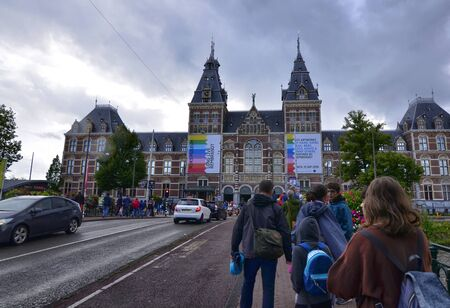 Amsterdam, Holland, August 2019. the imposing facade of the rijksmuseum characterized by red bricks. People cross the bridge with planters to visit it. Editorial