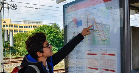 Amsterdam, the Netherlands, August 2019. A brown-haired Caucasian boy with glasses points to a point on the metro map.