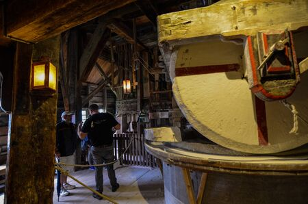 Zaanse Schans, Holland, August 2019.Northeast Amsterdam is a small community on the Zaan River.Visiting the inside of the mills we can see the millstone in action: the large round stones rotate slowly