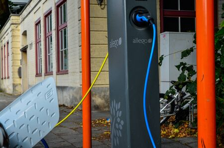 Bruges, Belgium. August 2019. A charging station for electric cars: a blue and a yellow cable are connected respectively to a hyundai and an electrically powered volkswagen. Redactioneel