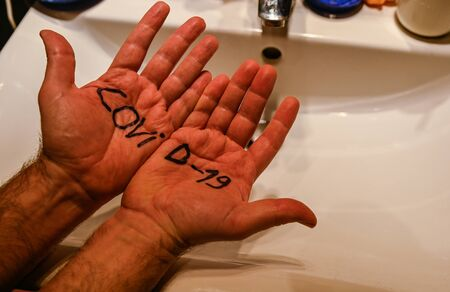 Coronavirus. Conceptual image of the danger of the virus: an inscription on the palms of the hands of a Caucasian man highlights how it attacks man. In the background, a sink for washing and cleaning.