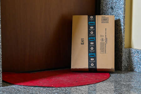 Turin, Piedmont, Italy. April 2020. Quarantine and social distance. The coronavirus causes amazon parcel deliveries to take place with the parcel left next to the customer's door, on the red carpet.