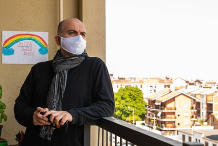 Turin, Piedmont, Italy. A Caucasian man wears a white mask, looks at nearby houses from the balcony during the flash mob for the coronavirus. On the wall the drawing with the rainbow.