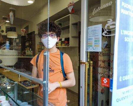 A Caucasian boy buys ice cream at the time of the coronavirus pandemic: he wears a white mask, the ice cream shop has a plexiglass separet to guarantee safety. You can see it between the boy's eyes.