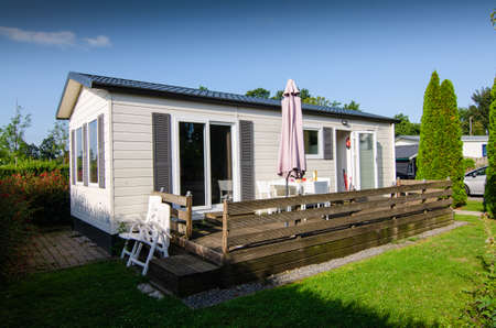 Netherlands, Zeeland region. August 2019. A nice campsite equipped with bungalows. Outside the house there is a small private garden, equipped with chairs and sun umbrella.