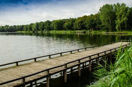 Netherlands, Zeeland region. August 2019. The beautiful pond of a campsite: the wooden pier goes into the water, in the background the forest runs alongside the shore.