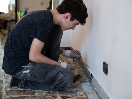 Masonry work in the apartment: a Caucasian boy is wearing work gloves and is using hammer and chisel to demolish the old baseboard.