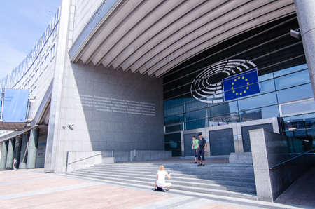 Brussels, Belgium, August 2019. External view of the modern metal and glass palaces which house the European Parliament. Entrance dedicated to Altiero Spinelli: tourists take souvenir photos.