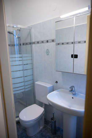 View of the interior of a bathroom from the entrance door. The yellow frame of the door is the frame: in evidence the mirror cabinet above the sink, on the left the toilet and the shower box.