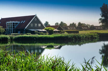 Netherlands, Goes. Dutch countryside lake landscape: reeds along the lake shore. Groups of characteristic chalets, one on the lake shore is reflected in the water. Beautiful summer day.