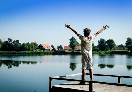 Netherlands, Goes. Dutch countryside lake landscape: reeds alternating with wooden piers. A Caucasian boy is inspired by nature and raises his arms to the sky.