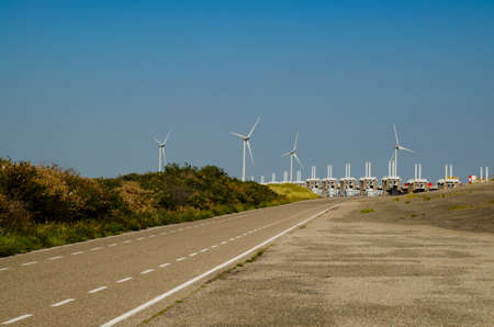 In Zeeland, wind farms are the setting for the immense dam that governs the flow of sea waters, securing the territory. Stockfoto