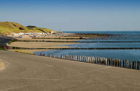 Westkapelle, The Netherlands, August 2019. The beaches of this location are wide and clean: on a beautiful sunny summer day a lot of people enjoy the sea. Characteristic are the wooden piling. Stockfoto