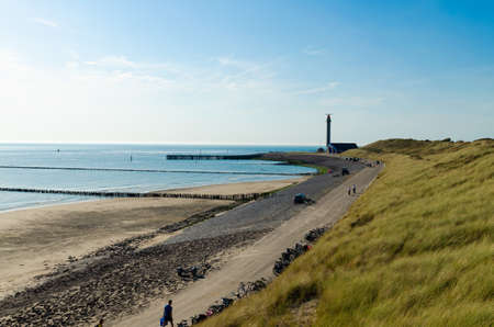 Westkapelle, Netherlands, August 2019. The beaches of this location are wide and clean: on a beautiful sunny day, the bike path along the sea has many bikes parked. The lighthouse in the background. Redactioneel