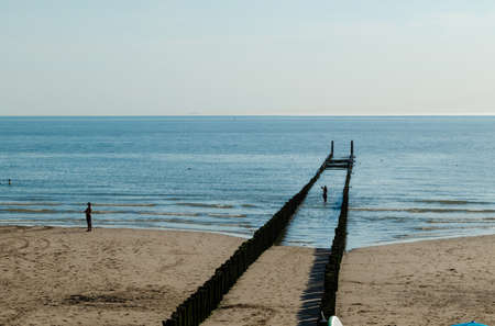Westkapelle, The Netherlands, August 2019. The beaches of this town are wide and clean, the long rows of poles that stretch towards the sea characterize the landscape. Beautiful sunny summer day