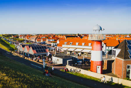 Westkapelle, The Netherlands, August 2019. The built-up area, below sea level, is protected by an artificial hill that surrounds it. On the top of the hill a red road. Redactioneel