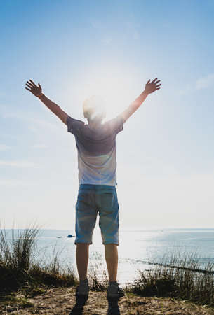 Netherlands, weastkapelle. North sea landscape. A Caucasian boy is inspired by nature and raises his arms to the sky. Stockfoto