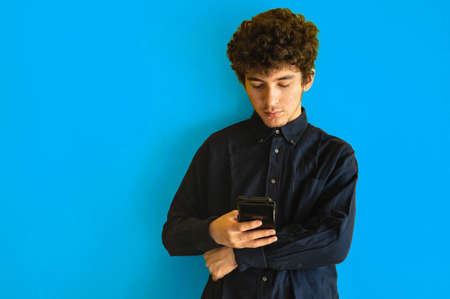 Cute brown curly haired boy with mobile phone on yellow studio background, he is using mobile applications or chatting with friends, copy space. Concept of using smartphone, addiction to gadgets.