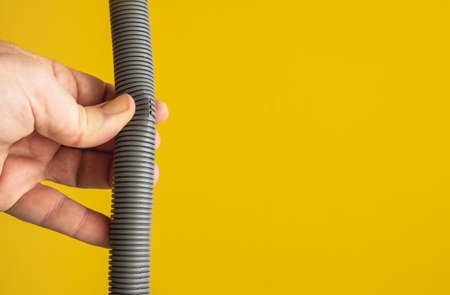 Against the yellow background the hands of a plumber are testing the integrity of a drain pipe: they highlight a crack that caused leaks and the replacement of the pipe.