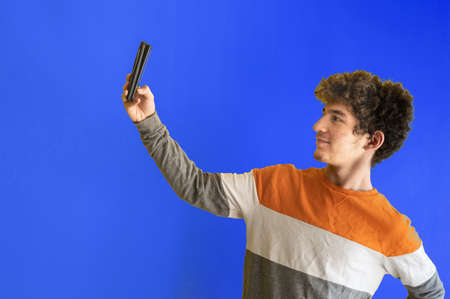 Cute brown curly haired caucasian boy on a yellow background, is posing with the smartphone camera to take a self-portrait. Copyspace Stockfoto