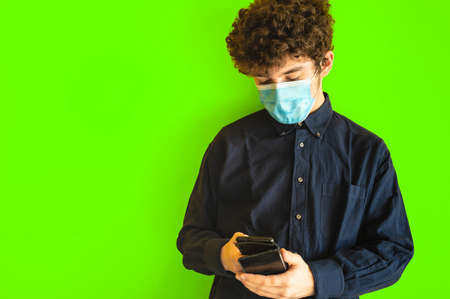 Cute brown curly haired boy with mobile phone on yellow studio background, he is using mobile applications or chatting with friends. He has the mask to defend himself from the coronavirus.