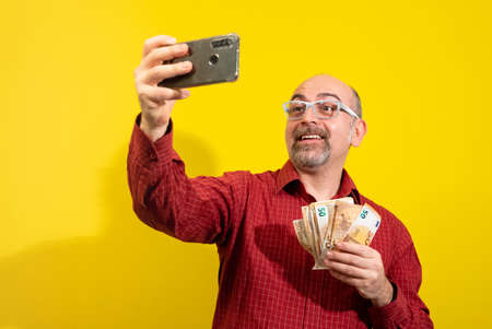 Middle-aged Caucasian man holding a bunch of 50 euro bills in one hand and taking a selfie with the other. He is happily surprised. Concept of winning, luck and wealth. Yellow background. Stockfoto