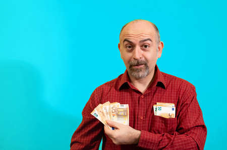 Middle-aged Caucasian man holding a bunch of 50 euro bills in his hand and has more in his shirt pocket. He is happily surprised. Concept of winning, luck and wealth. Yellow background.