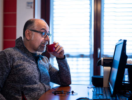 A middle aged caucasian man working from home, while drinking a coffee, is pleasantly surprised by a notification that reads on his computer monitor.