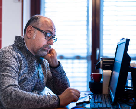 A middle aged caucasian man working from home, is pissed off and feels isolated. Concept of stressful and demeaning work.