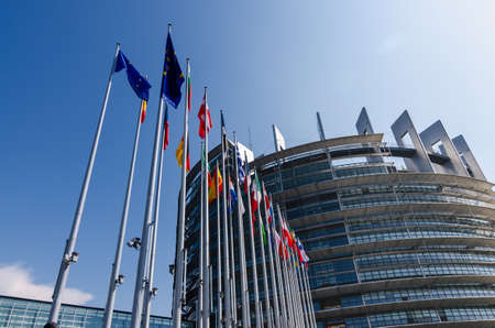 Strasbourg, France. August 2019.The entrance to the modern seat of the European parliament. A row of flagpoles with the flags of the member states of the European Union welcomes those who enter.