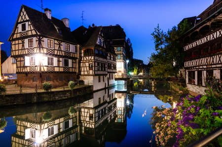 Strasbourg, France, August 2019. In the heart of the historic center, an enchanting glimpse of the canals where the typical historic houses are reflected. At the blue hour it has its greatest charm.