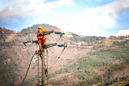 Man at work. Technicians are repairing high voltage transmission systems on the power poles.
