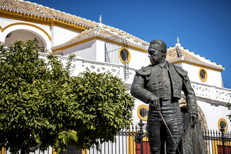 Seville, Andalusia, Spain: The statue of Curro Romero, a famous torero from Seville, in front of the Plaza de Toros de la Maestranza Stock Photo