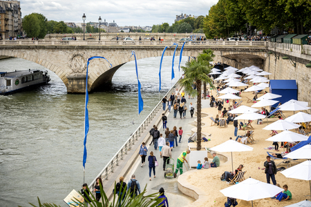 Paris, tourists relaxing under the beach umbrellas, along the Parc des River de Seine. Pont au Change in the background. France.