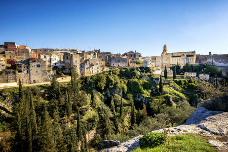 Gravina in Puglia: picturesque landscape of the the deep ravine and the old town with the ancient cathedral, Bari, Italy