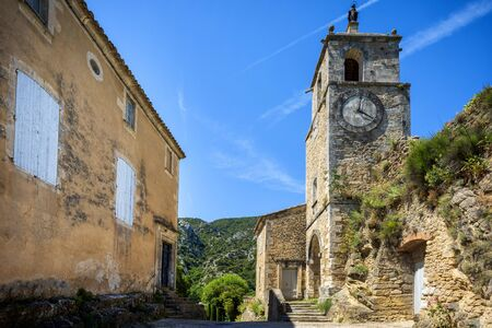 The minuscule old hilltop village of Maubec-Vieux. A magnificent clock tower, topped by a statue of the Virgin, in the small hilltop village Maubec-Vieux, Luberon, Provence, France
