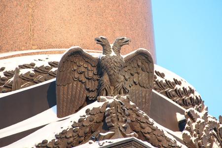Russian palace: Cerrar los detalles decoraciones columna Alexander con el s�mbolo imperial �guila bic�fala rusa cubierto de nieve en el cuadrado del palacio en el fondo de cielo azul, San Petersburgo, Rusia