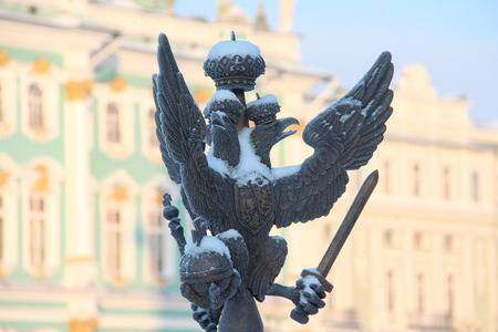 double headed eagle: Close up details fence decorations with the Russian imperial double-headed eagle symbol covered with snow on Palace Square on the background of the Hermitage, St. Petersburg, Russia Stock Photo