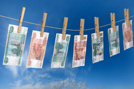 3d illustration: crumpled banknote of roubles to dry on the rope clothes pins attached, business concept, russian money laundering, offshore, illicit black cash. Blue sky background.