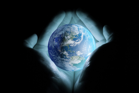 Mens hands holding the planet earth rotated the continents of North and South America with a blue glow on a black background.