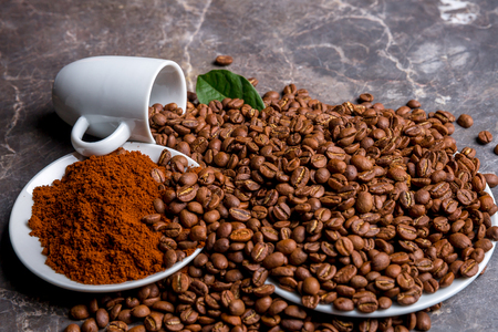 A cup, roasted coffee beans and ground coffee on a marble table Stock Photo