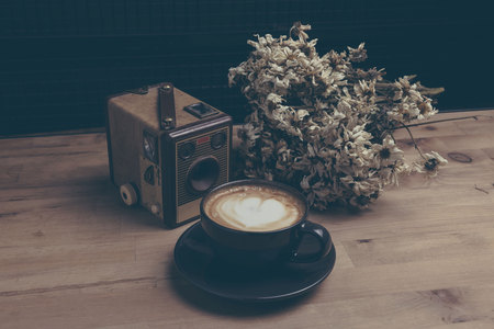 Coffe latte, an old camera and dried daisies on a wooden table. Sepia tinted.