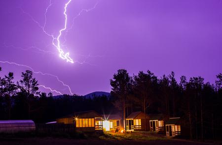Lightning in the night sky over houses. Lightning Bolt Strike, storm.
