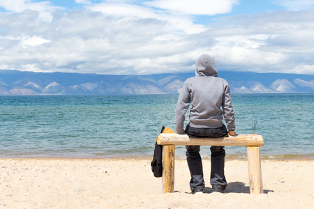 Man or woman is sitting in a hoodie on the beach. Back view