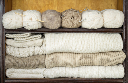 Shelves filled by balls of wool, knitting needles, ready woolen fabrics Фото со стока