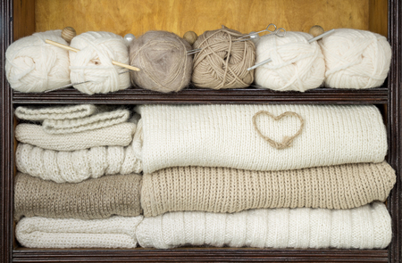 Shelves filled by balls of wool, knitting needles, woolen fabrics, decorations