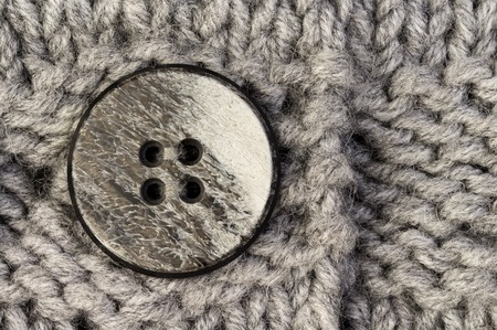 Button on gray knitted fabric