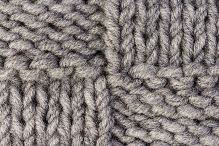 Knitting. Gray knitted pattern background or knit fabric texture background Фото со стока