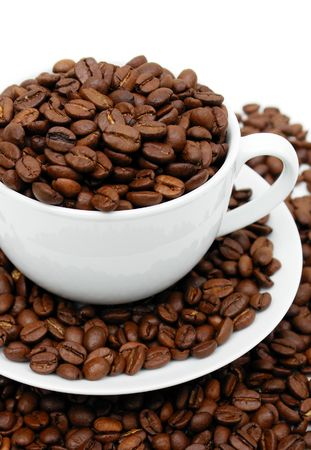Cup on saucer overflowing with coffee beans, set against white background.