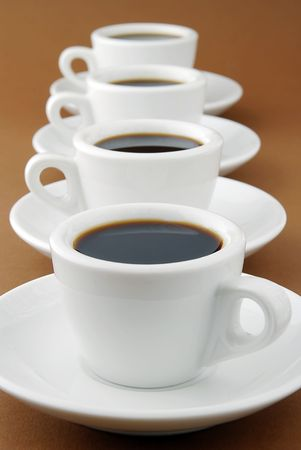 a row of full espresso cups on saucers
